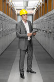 Full length of young male supervisor with digital tablet examining machines in control room Stock Photography