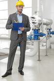 Full length of young male supervisor writing on clipboard by industrial machinery Royalty Free Stock Photos