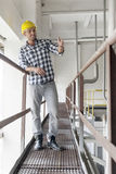 Full length of young male worker gesturing on metal aisle in industry Stock Image