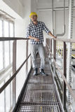 Full length of young male worker standing on metal aisle in industry Royalty Free Stock Photo