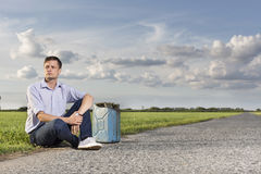 Full length of young man with empty gas can sitting by country road Stock Image