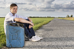 Full length of young man with empty gas can sitting by road Royalty Free Stock Photos