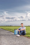 Full length of young man with empty petrol can sitting by country road Stock Photo