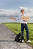 Full length of young man hitching while holding anywhere sign on countryside Royalty Free Stock Photography