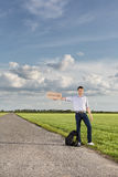 Full length of young man holding anywhere sign on empty road Stock Photography