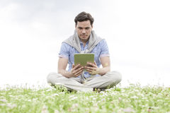 Full length of young man holding digital tablet while sitting on grass against sky Royalty Free Stock Photography
