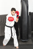 Full length of young man in kimono throwing punches Royalty Free Stock Photo