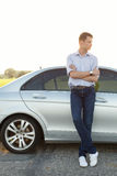 Full length of young man looking away while standing by car at countryside. Full length of young men looking away while standing by car at countryside Royalty Free Stock Images