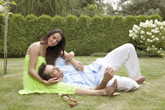 Full length of young man lying on woman's lap in park Royalty Free Stock Images