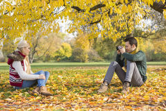 Full length of young man photographing woman in park during autumn Stock Photos