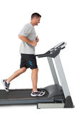 Full length of a young man running on a treadmill Stock Photography