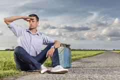 Full length of young man shielding eyes while sitting with petrol can by country road Royalty Free Stock Photos