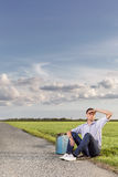 Full length of young man shielding eyes while sitting with petrol can on country road Royalty Free Stock Photography