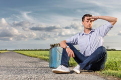 Full length of young man shielding eyes while sitting with petrol can by country road Stock Photo