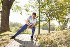 Full length of young man stretching on path in park Stock Images