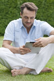 Full length of young man using digital tablet in park Stock Photography