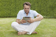 Full length of young man using digital tablet in park Royalty Free Stock Photography