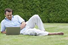 Full length of young man using laptop while lying on grass in park Royalty Free Stock Images