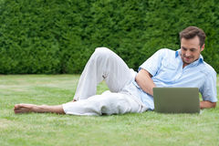 Full length of young man using laptop while lying on grass in park Royalty Free Stock Image