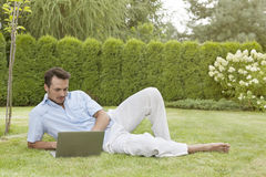 Full length of young man using laptop while reclining in park Royalty Free Stock Image