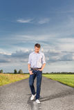 Full length of young man walking on empty rural road Stock Images