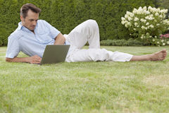 Full length of young man working on laptop in park Royalty Free Stock Image