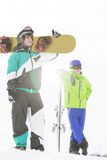 Full length of young men with snowboards in snow Royalty Free Stock Image