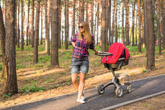 Full length of young mother with a stroller in the park stock images