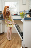 Full length of a young redheaded woman looking into an open oven Royalty Free Stock Image