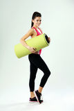 Full-length of a young sport woman with yoga mat Royalty Free Stock Photo