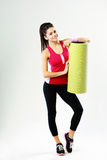 Full-length of a young sport woman with yoga mat Stock Image