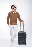 Full length of young tourist asian man holding passport with sui. Tcase over grey background Stock Image