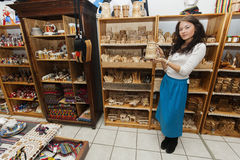 Full length of young woman displaying product in gift store Royalty Free Stock Photos