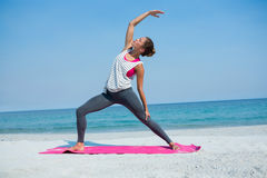 Full length of young woman exercising on mat at beach Royalty Free Stock Photography