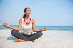 Full length of young woman with eyes closed meditating at beach Royalty Free Stock Photography