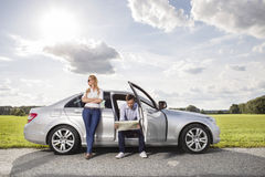 Full length of young woman looking away while man reading map in car at countryside Stock Images