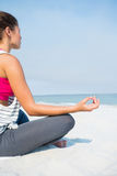 Full length of young woman meditating on sand at beach. Against sky during sunny day Stock Photography