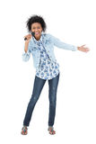 Full length of a young woman singing into a microphone Royalty Free Stock Photos