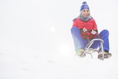 Full length of young woman sledging in snow Stock Images