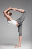 Full length of a young woman stretching body. Gray Background. Royalty Free Stock Photos