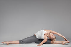 Full length of a young woman stretching body. Gray Background. Stock Image