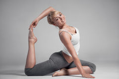 Full length of a young woman stretching body. Gray Background. Royalty Free Stock Image