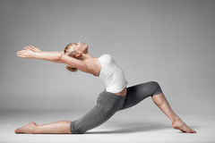 Full length of a young woman stretching body. Gray Background. Royalty Free Stock Images