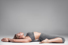 Full length of a young woman stretching body. Gray Background. Stock Photo