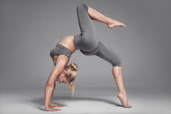 Full length of a young woman stretching body. Gray Background. Stock Images