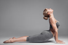Full length of a young woman stretching body. Gray Background. Royalty Free Stock Photography
