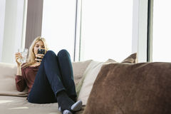Full length of young woman text messaging at home Royalty Free Stock Photos
