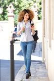 Full length young woman walking in city with mobile phone and juice Royalty Free Stock Photo