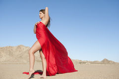 Full length of a young woman wrapped in red cloth on arid landscape Royalty Free Stock Photo