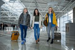 Glad friends with cases moving to aircraft. Full length of young women with luggage going for plane. They are looking at camera with enjoyment Royalty Free Stock Photography